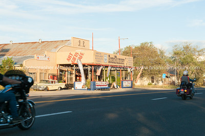 Bikers arrive while morning shade still covers street in Seligman, Arizona, USA