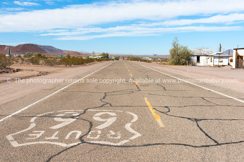 Cracked section of Route 66 road with shield at Ludlow, California, USA.
