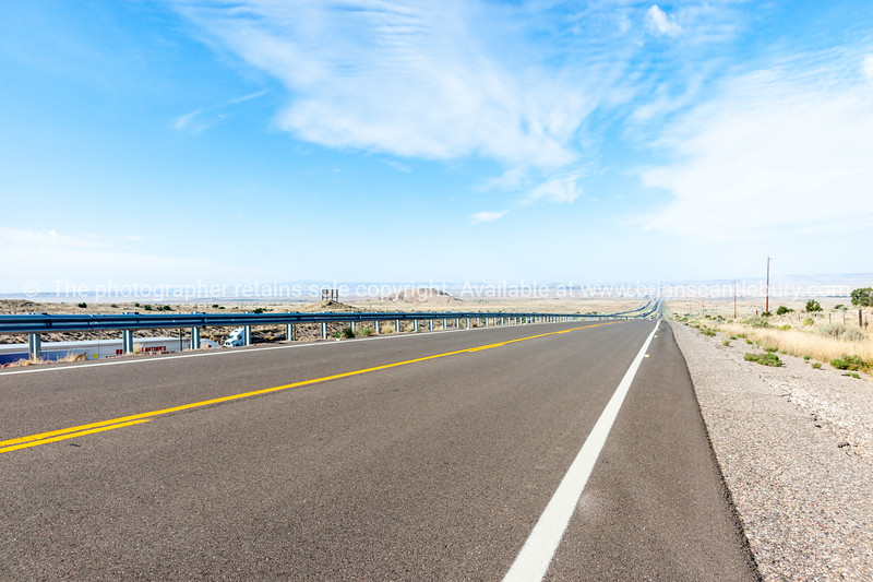 Long straight road ahead throgh desert of New Mexico, USA.