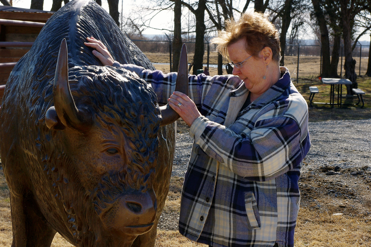 "Rita petting a bronze bison; Buffalo Ranch, Afton, Oklahoma. <br /> <br /> The old Buffalo Ranch included a Trading Post, Western Wear Store, BBQ, and the Dairy Ranch, plus 30-40 bison (per ""Images of Route 66"" by David Wickline). The newer establishment keeps only a few live bison near the multifunction gas station/tourist trap."