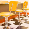 Three stool on chrome bases at counter on black and white checkered floor in diner in Albuquerque, New Mexico, USA
