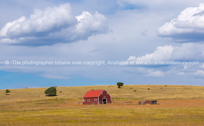 Rural scene, red barn in field under cloudy sky along Route 66