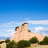Landscape, red buttes in green landscape under blue sky.