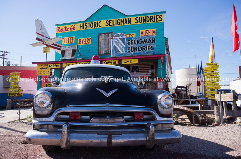 Old Chrrysler police car outside Route 66 Historic Seligman Sundries shop.