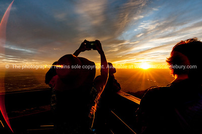 Tourists watch and photograph brilliant sunset from Sandia Peak, Albuquerque, New Mexico, USA.
