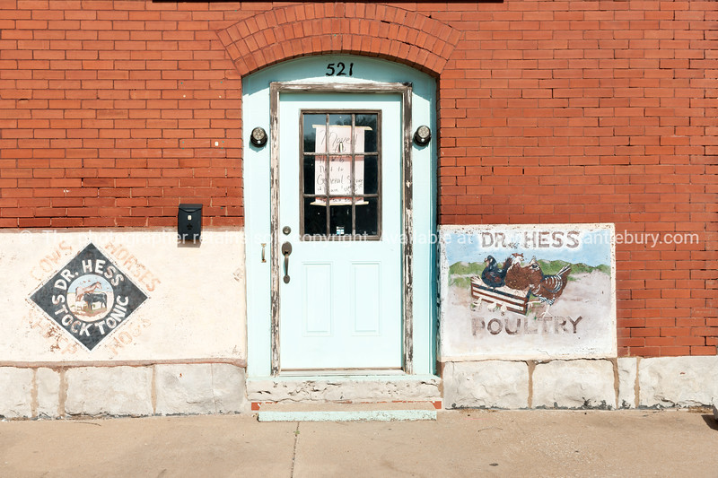 Buidlings,  Dr. Hess Poultry and faded green door in brick exterior wall Chelsea, Oklahoma on Route 66.