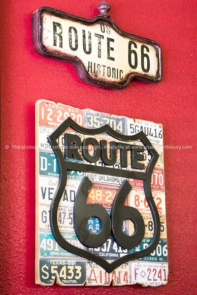Route 66 sign on red wall, one of the incredible variety of 66 signs seen along the historic route