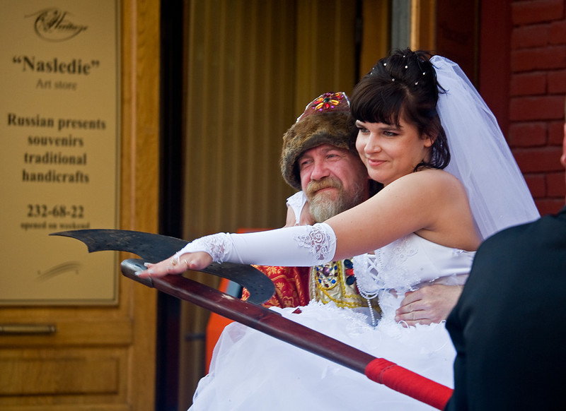 Bride on Cossack arms while groom guards the price with ax.