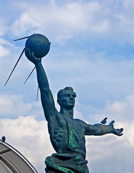 Soviet area statue of man holding Sputnik.