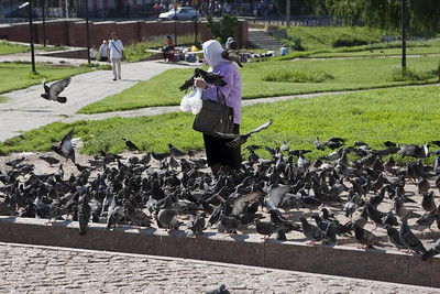 Feeding pigeons outside Holy Trinity Lavra Monastery