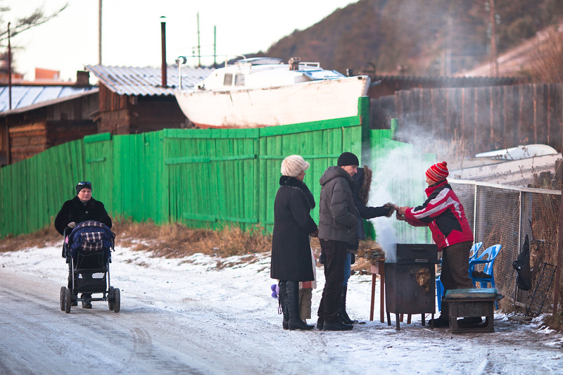 Locals selling locally-caught and cooked fish in the village of Lystvianka on the shores of Lake Baikal, Siberia.