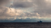 A fishing boat passes in front of the mountains on Lake Baikal, Siberia.