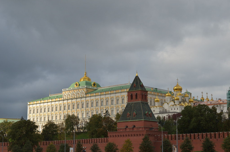 Wall and tower of the Kremlin with the Grand Kremlin Palace behind <br /> and Golden Domes of the Cathedral of the Annunciation to the right.<br /> Moscow - September 21, 2011