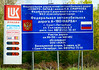"""OAT Trip/Poland-Lithuania-Latvia-Estonia-Russia/13 Sep-02 Oct 2016.  Russia.  St. Petersburg.  Enroute from Narva to St. Petersburg.  A sign.  Hmmmm..... methinks something like """"Your highway taxes at work""""?  <br /> Very rough translation:  The Federal Highway Administration """"NORTH ZAHAD"""" N.V.SMIRNOVA behalf of the Federal Road Agency Federal Highway A-180 """"Narva"""" St. Petersburg street. Sezzhinskaya d.3 VAR. Tel. 8(812)232-10-61 Road section km 99+150 -  km 148+402 services of """"ESCO"""" Vasilevsky Island, 5-line, 32, St. Petersburg, tel. 8(81375)2-73-51."""