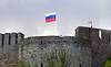 OAT Trip/Poland-Lithuania-Latvia-Estonia-Russia/13 Sep-02 Oct 2016.  Russia.  St. Petersburg.  As we cross the border at Narva, from Estonia into Russia, we see the Russian flag flying over Ivangorod Fortress just on the Russian side of the Narva River.