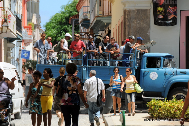 A truckload of workers cuts through a narrow street in Old Havana.