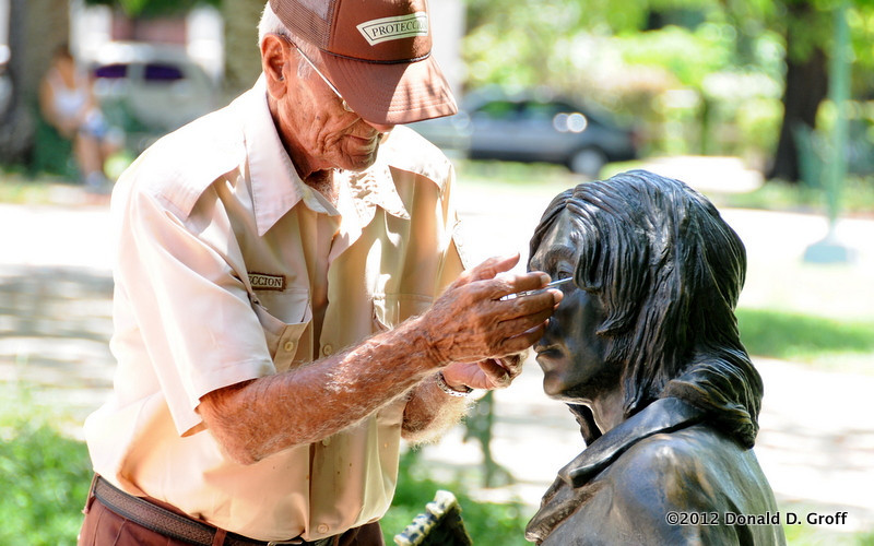 A park employee at Lennon Park, in the Vedado section of Havana, affixes wire-rim glasses to the face of the John Lennon statue.