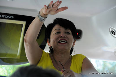Dr. Gloria Bonilla directs from the front of tour bus.