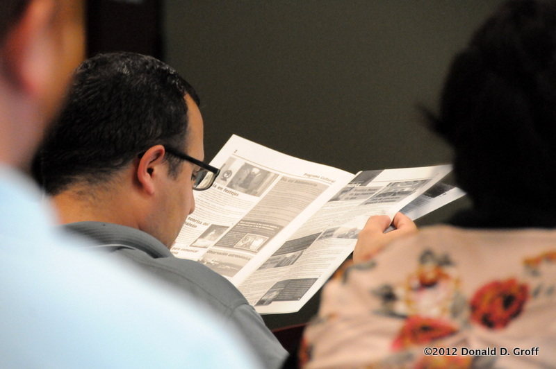Assistant Professor Eduardo Gomez digests a newsletter while awaiting a speaker.