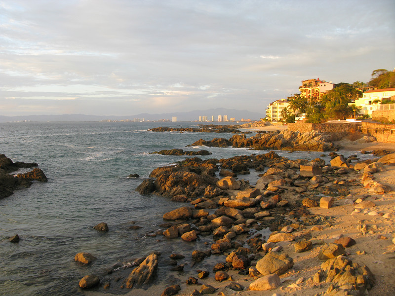 This rocky cove is actually in Conchas Chinas, site of elegant condos and upscale restaurants.  It's a few miles south of Puerto Vallarta, which you can see in the distance.