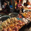 Waiting for customers at a fresh food corner in Kampot market, Cambodia