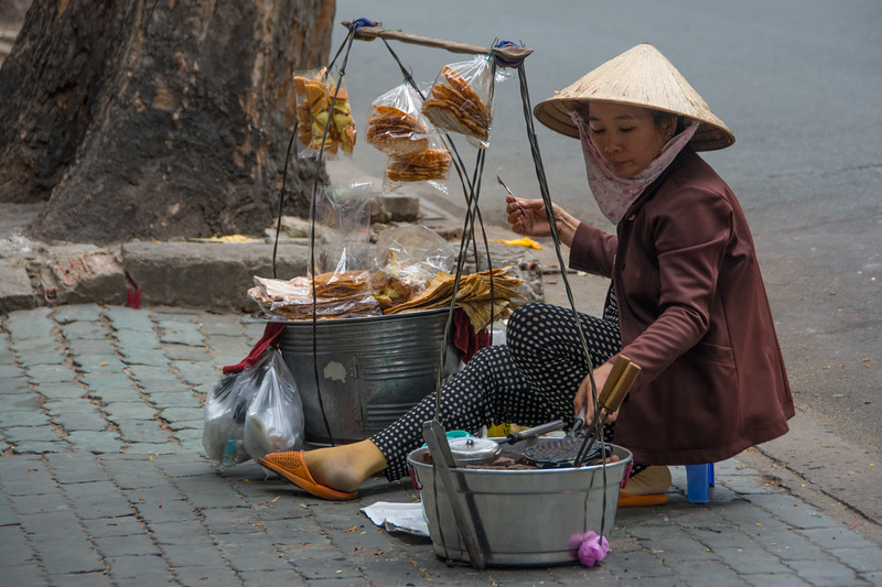 A woman prepares treats made from dried bananas squashed into a flat sheet, on the streets of Ho Chi Minh City (Saigon), Vietnam, May 2015. [Ho Chi Minh City 2015-05 022 Vietnam]