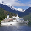 Voyages of Discovery, MV Discovery at anchor in Geirangerfjord, Norway. With gangway and lifeboats lowered.