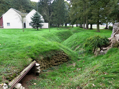 Trenches at Newfoundland Park. The Visitor Centre in the background is in the style of a typical Newfoundland wooden house.