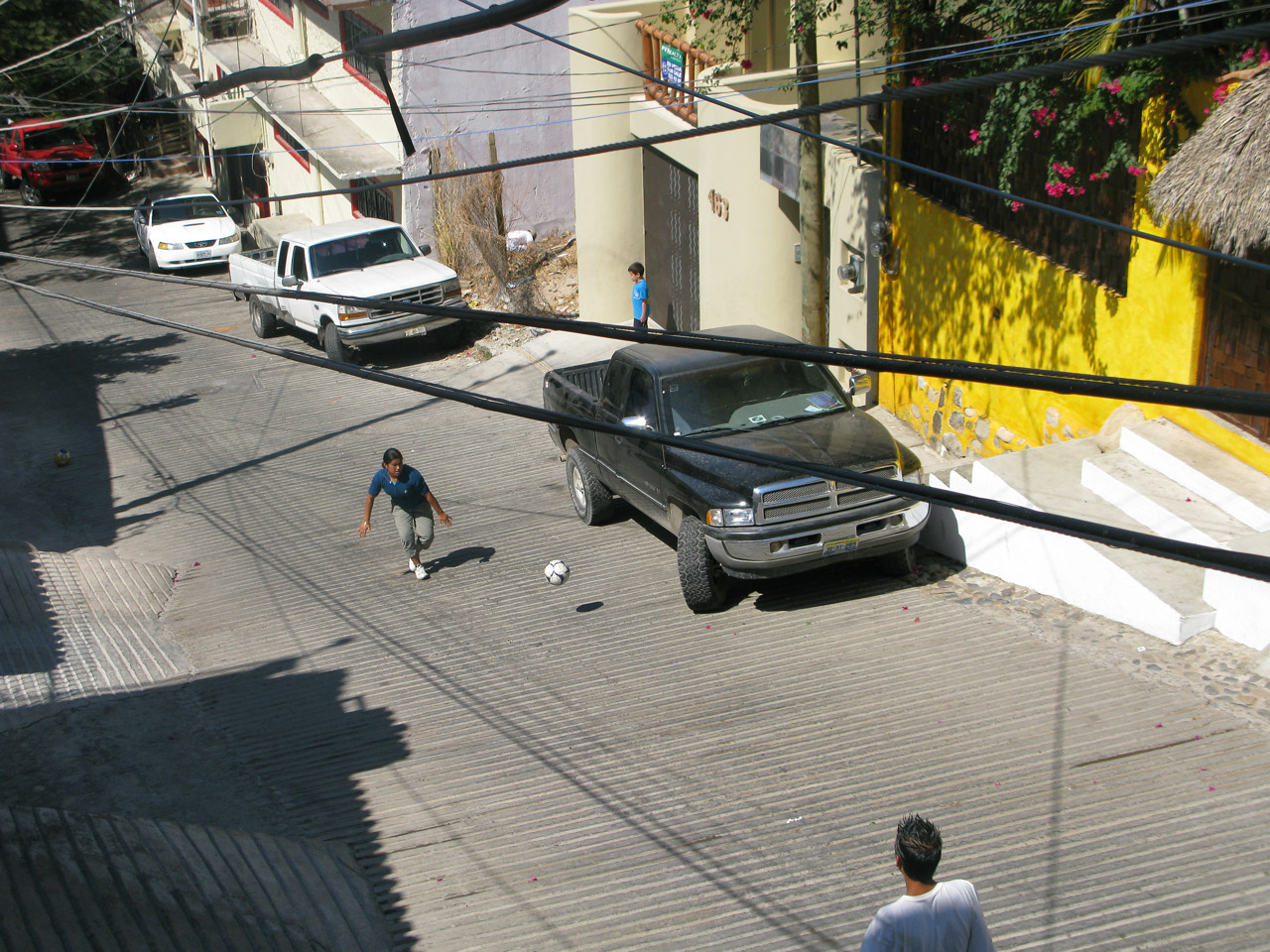 Believe it or not, the neighborhood kids had a rambunctious game of soccer on the steep street outside my apartment last Sunday morning.  The next photos show more of the game, which I tried to video and couldn't keep focused on the ball!