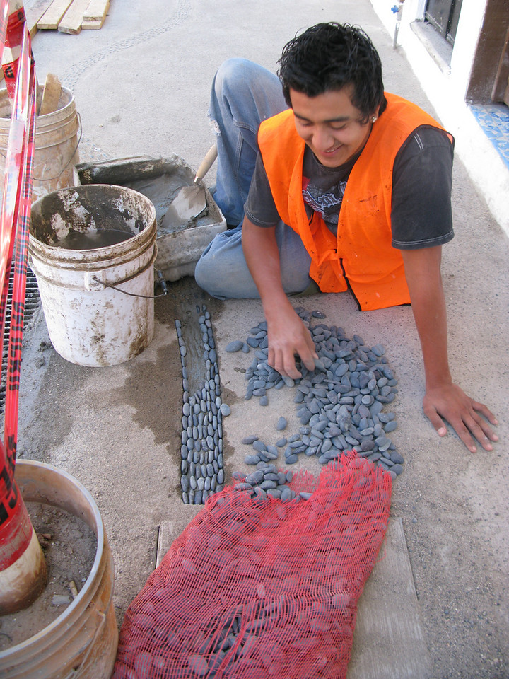Once the concrete is poured and the channel is formed, workers place every stone BY HAND and then add concrete to fix them.