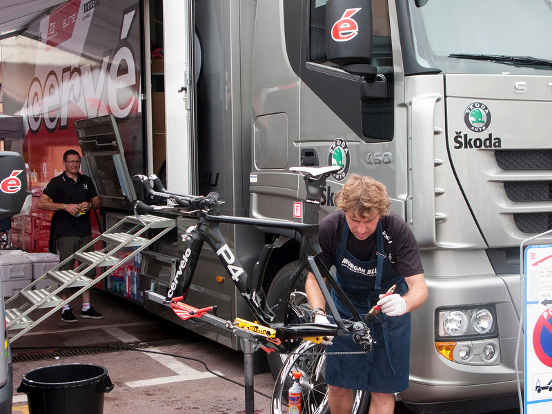 Team Cervelo mechanic cleans the drive train of one of the time trial bikes