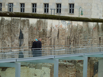 The former Prison cell walls in the former Gestapo Headquarter below the walkway with a remnant of the Berlin Wall in the background.