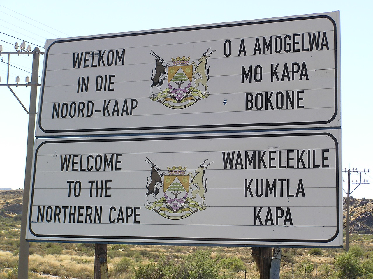 Multilingual highway signs - English, Afrikaans, Xhosa and ?<br /> <br /> At the Three Sisters, we were happy to leave the busy N1 highway and start our journey north along the N12 towards the town of Upington, which lies 620km to the north of Karoo National Park. We were to spend the night in Upington before venturing into Kgalagadi Transfrontier Park. At the Three Sisters, we left the Western Cape (province) and crossed into the Northern Cape.