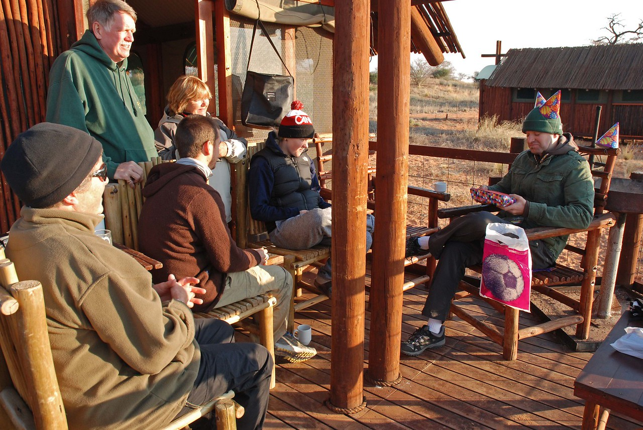 Winter in the Kalahari - warmly dressed for breakfast at sunrise on Graham's birthday<br /> <br /> We visited the park in winter, which in the Kalahari Desert is from May to August. It is a cool, dry season, when temperatures at night often fall below zero and frost is common. The temperature has been known to fall as low as -11oC and, after a particularly cold night at one camp, we did wake to thick frost on the windshield of the 4x4. We slept in long underwear, socks and toques. In the morning, it was challenging to crawl out from under the warm duvets and heavy blankets. Showering in the morning was out of the question. It was too blessed cold! We would often wear gloves while eating breakfast. Temperatures during the day were very comfortable, rising surprisingly quickly in the morning to the mid-twenties. By lunch, we had usually stripped down to shorts and T-shirts. <br /> <br /> Kgalagadi, a semi-arid region, receives only 150mm of rain annually, mostly during dramatic thunderstorms between November and April. As it is dry in winter, the animals are forced to congregate around the waterholes, which makes game viewing easier. This is why we visit the park in winter. Although the park's policy is minimal interference, artificial water is supplied to the animals because of human settlements and fences that prevent access to natural, permanent water sources. While we experienced no rainfall, we did find the typically clear, cobalt blue skies to be quite cloudy and grey at times - unusual at that time of year. <br /> <br /> Robert, Laura and I first visited Kgalagadi Transfrontier Park in November 2004, during our previous sabbatical in Cape Town. We had returned in August 2007, as our first visit to the park had been a highlight of our year in South Africa. It is our favourite South African national park, and we were looking forward to our return.