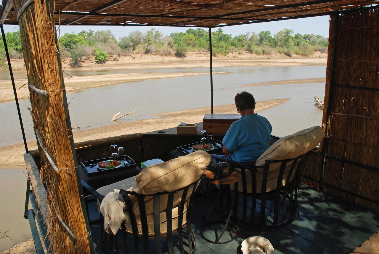Lunch at Kaingo Camp<br /> <br /> Lunch at Kaingo Camp in South Luangwa National Park - brought to the deck of our chalet/tent. From this relaxing vantage point overlooking the Luangwa River, we enjoyed delicious midday meals while watching puku coming down to the river to drink, hippos and crocodiles basking in the sun, kingfishers diving, storks fishing and elephants crossing the river. Such a memorable way to enjoy our midday meal!