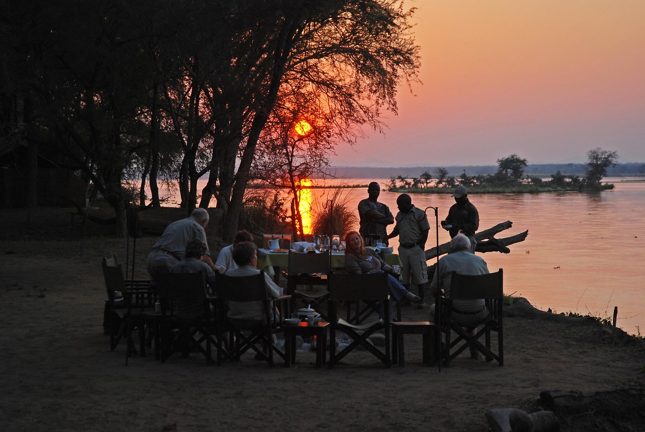 Breakfast beside the Zambezi at Old Mondoro at sunrise - such a memorable way to start the day!<br /> <br /> Despite the early hour (5:30am), breakfasts at Old Mondoro ensured that our days started out well. The first meal of the day was served around the campfire on the banks of the Zambezi River. We would sit and watch the sun rise over the Zambezi as we enjoyed a delicious breakfast of fresh fruit, yogurt, muesli, cereals, freshly baked muffins, toast expertly cooked over the fire by the guides, and the best porridge I have ever eaten - kept warm over the fire in a potjie. Delicious food in a spectacular setting with great company!