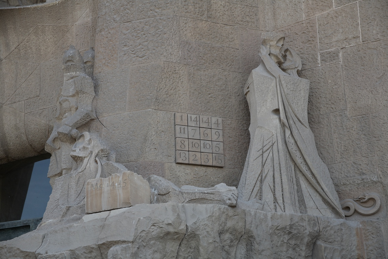 This part of the Passion Facade shows Judas giving Christ a kiss so the soldiers know who to arrest.<br /> <br /> The grid with numbers adds up to 33 in several different combinations. This is Christ's age when he was crucified.