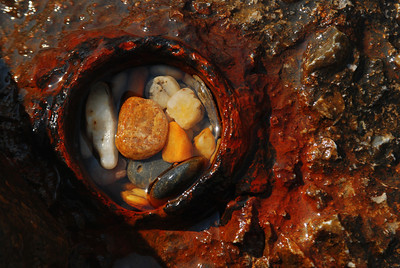 Stones in an old pipe.  The red is not rust but some marine growth.