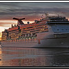 A Carnival Cruise ship leaving port at sunset
