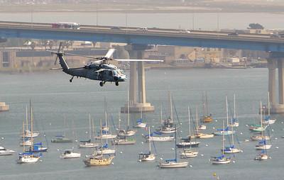 SH--60 helicopter flying past the Coronado Bay Bridge.