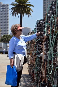 Mom, investigating the lobster traps stacked on a pier in San Diego.