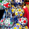 Soccer balls hanging at one of the shops near their apartment.
