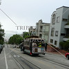 A cable car goes up the street in San Francisco, California.