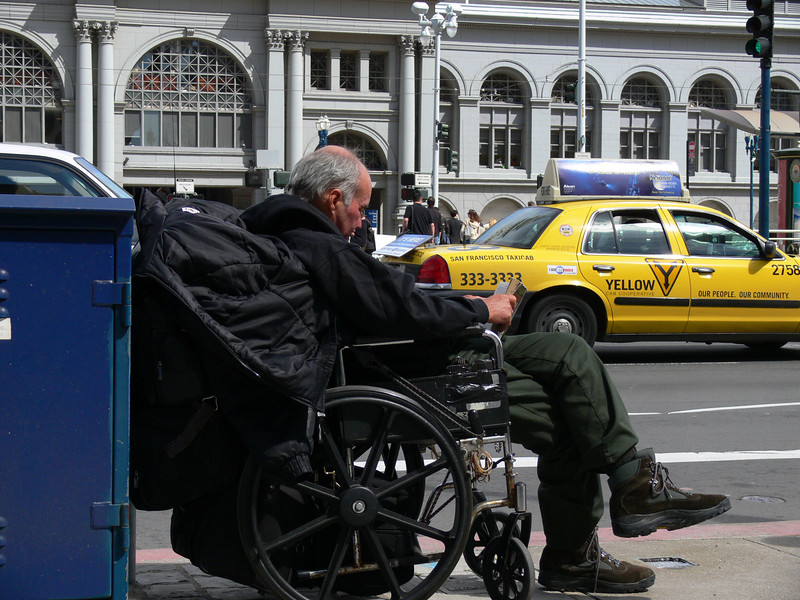 Some random wheelchair dude chillin' reading his book by the road