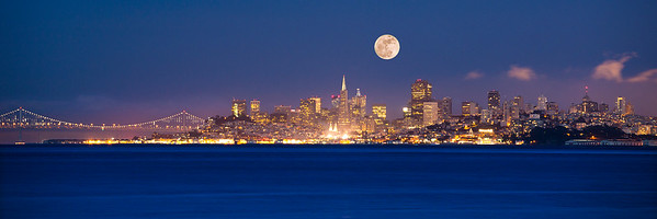 "Full Moon rises over the San Francisco skyline as evening settles over the City as seen from Sausalito.The format of this image has been cropped to yield a dramatic and panoramic 12"" x 36"" print on paper or on metal."