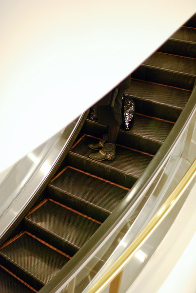 """<span id=""""title"""">Boots</span> The wearer of these boots is riding down one of the curved escalators in the Westfield"""