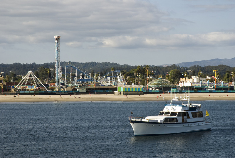 "Motoryacht anchoring off the Santa Cruz beach with the Boardwalk's historic roller-coaster ""Giant Dipper"" in the background."