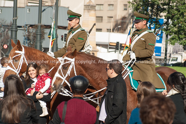 Mounted Police and tourists pose for photographs in the sqaure outside the Presidential Palace, la moneda.