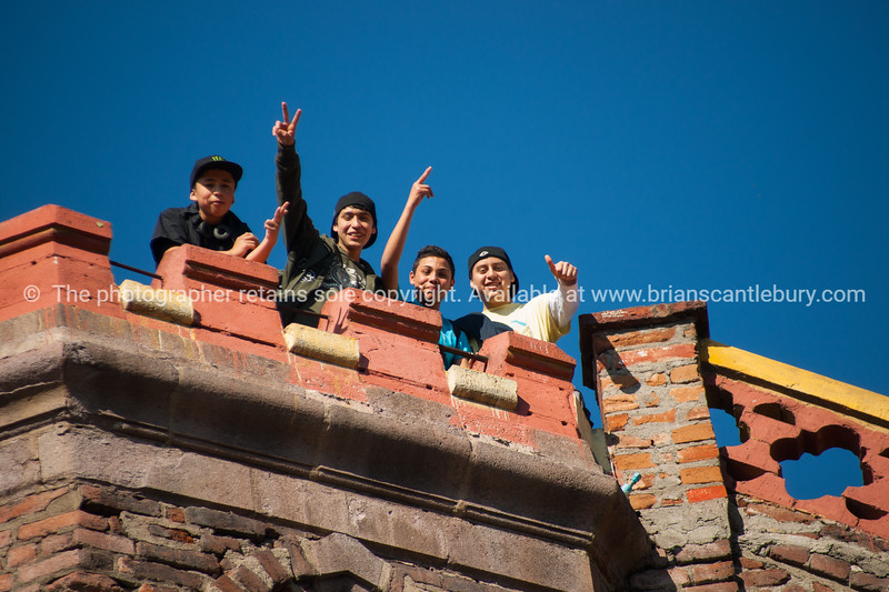 Street scenes and buildings.Santiago de Chile. Youth display their exuberance, waving out from atop the historic fortress Hildago, Cerro Santa Lucia.