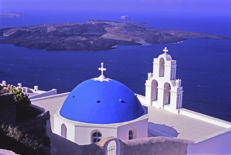 The Classic Postcard shot.  <br /> Chapel with blue dome and three bells over looks the caldera and volcano.<br /> Santorini, Greece<br /> April 2006<br /> © WEOttinger, The Wildflower Hunter - All rights reserved<br /> For educational use only - this image, or derivative works, can not be used, published, distributed or sold without written permission of the owner.